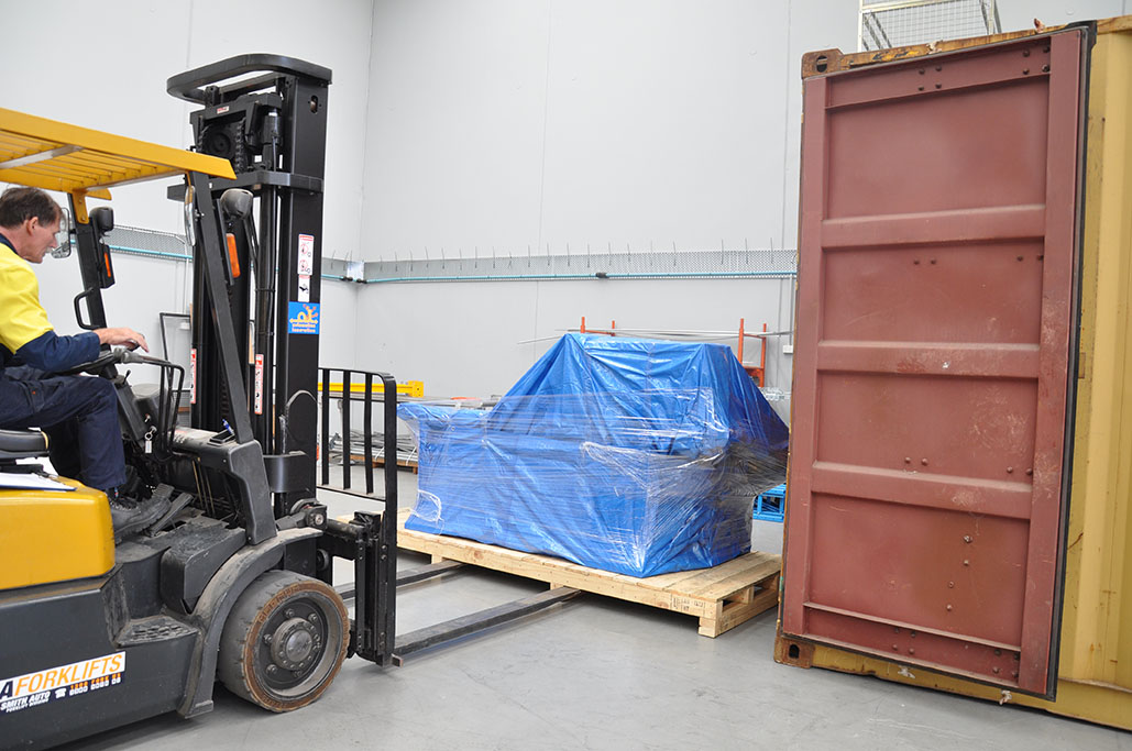 A picture of Warehouse Manager placing wrapped packaged in shipping container